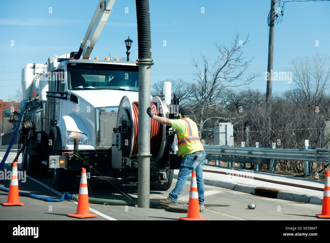 Man guiding large vacuum on a truck into sewer for cleaning out debris. St Paul Minnesota MN USA Stock Photo