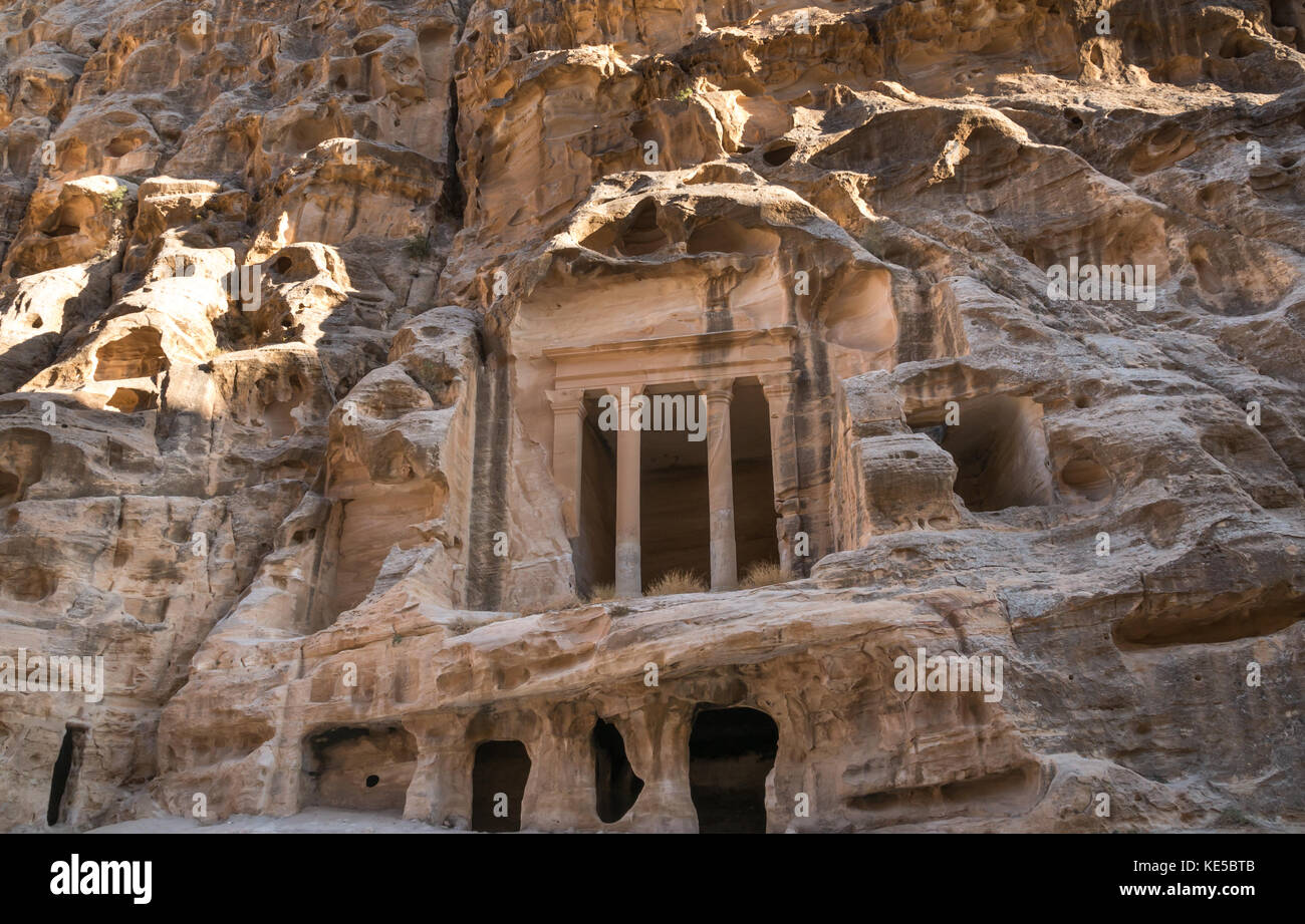 Nabataean Triclinium ruin carved in red sandstone cliff, Little Petra gorge, Siq al-Barid, archaeological site, - Stock Image