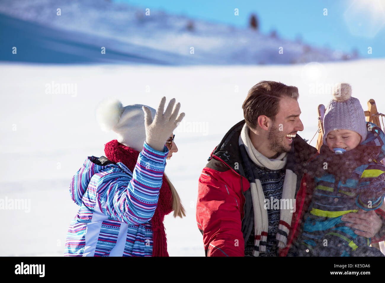 the happy family rides the sledge in the winter wood, cheerful winter entertainments - Stock Image