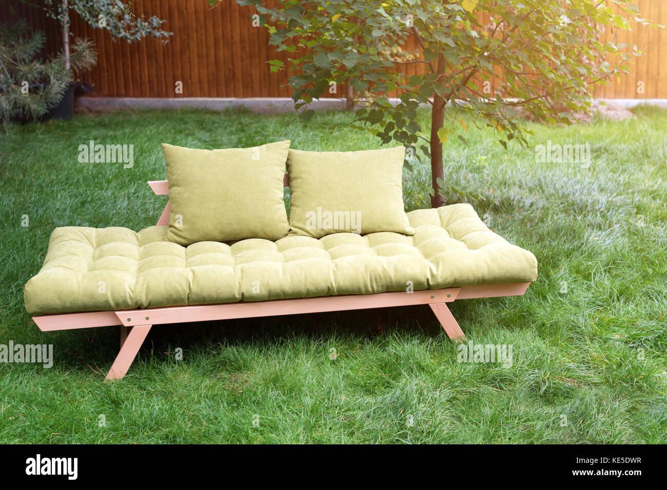 Green Sofa In The Yard Outdoors. Outdoor Furniture In Green Garden Patio.    Stock