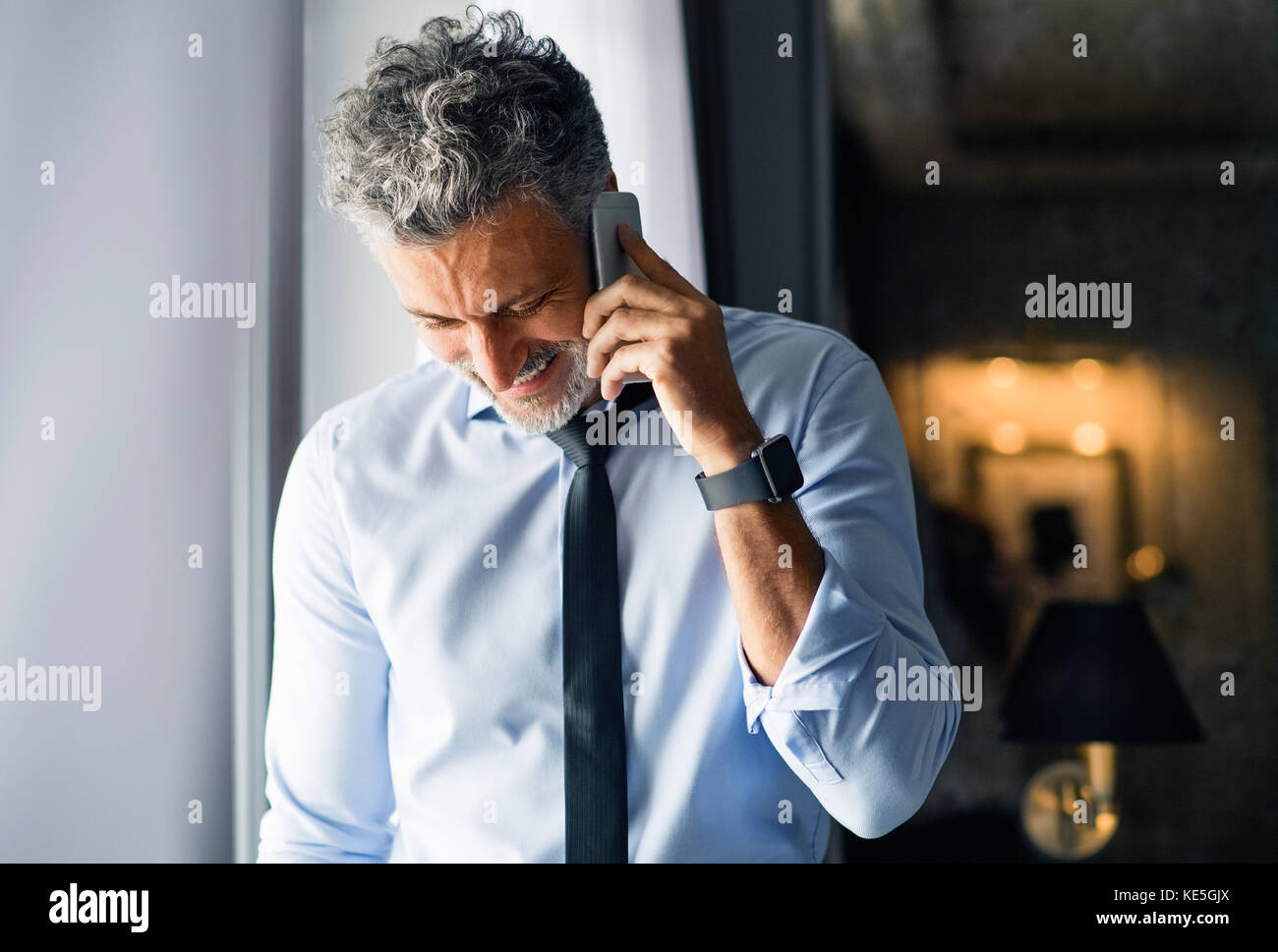Mature businessman with smartphone in a hotel room. - Stock Image