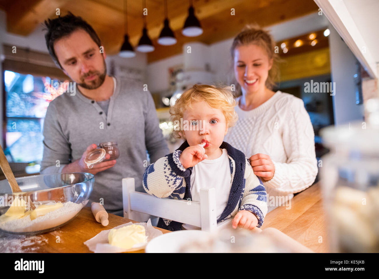 Young family making cookies at home. Stock Photo