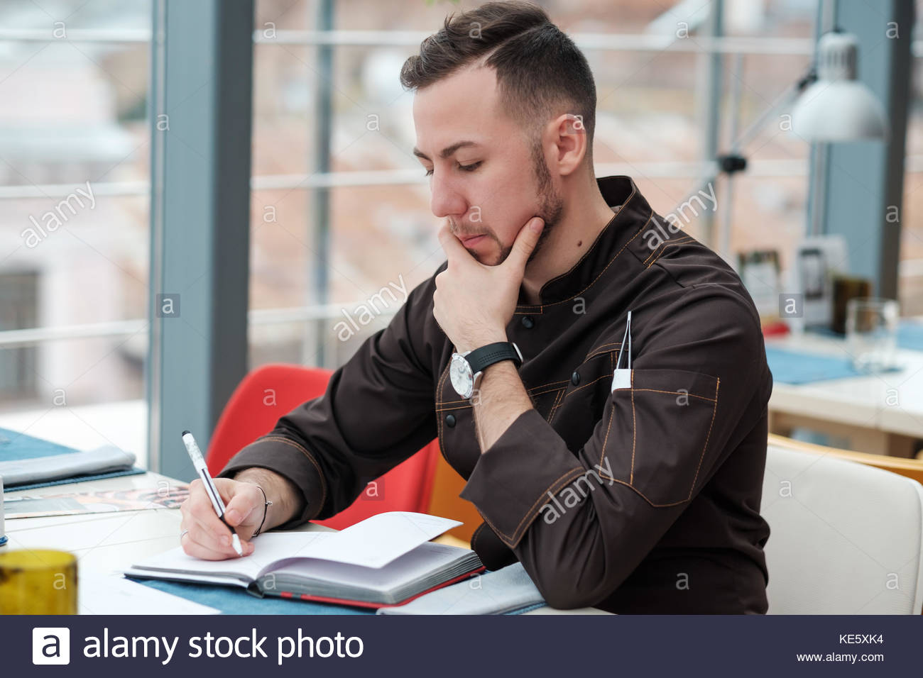 Caucasian male chef cook thinking about new menu or recepts. - Stock Image
