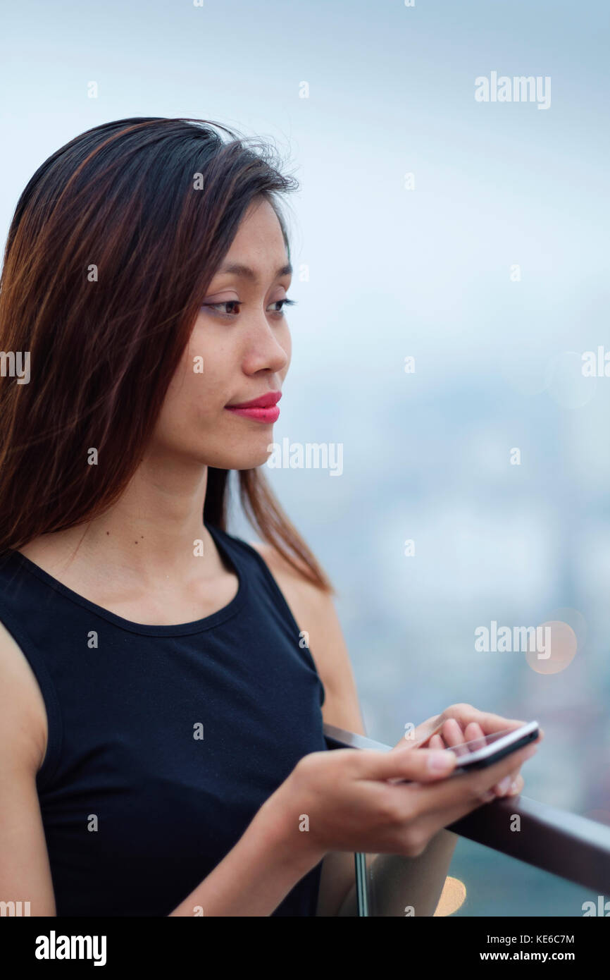 Young Asian Woman on her Cell Phone - Stock Image
