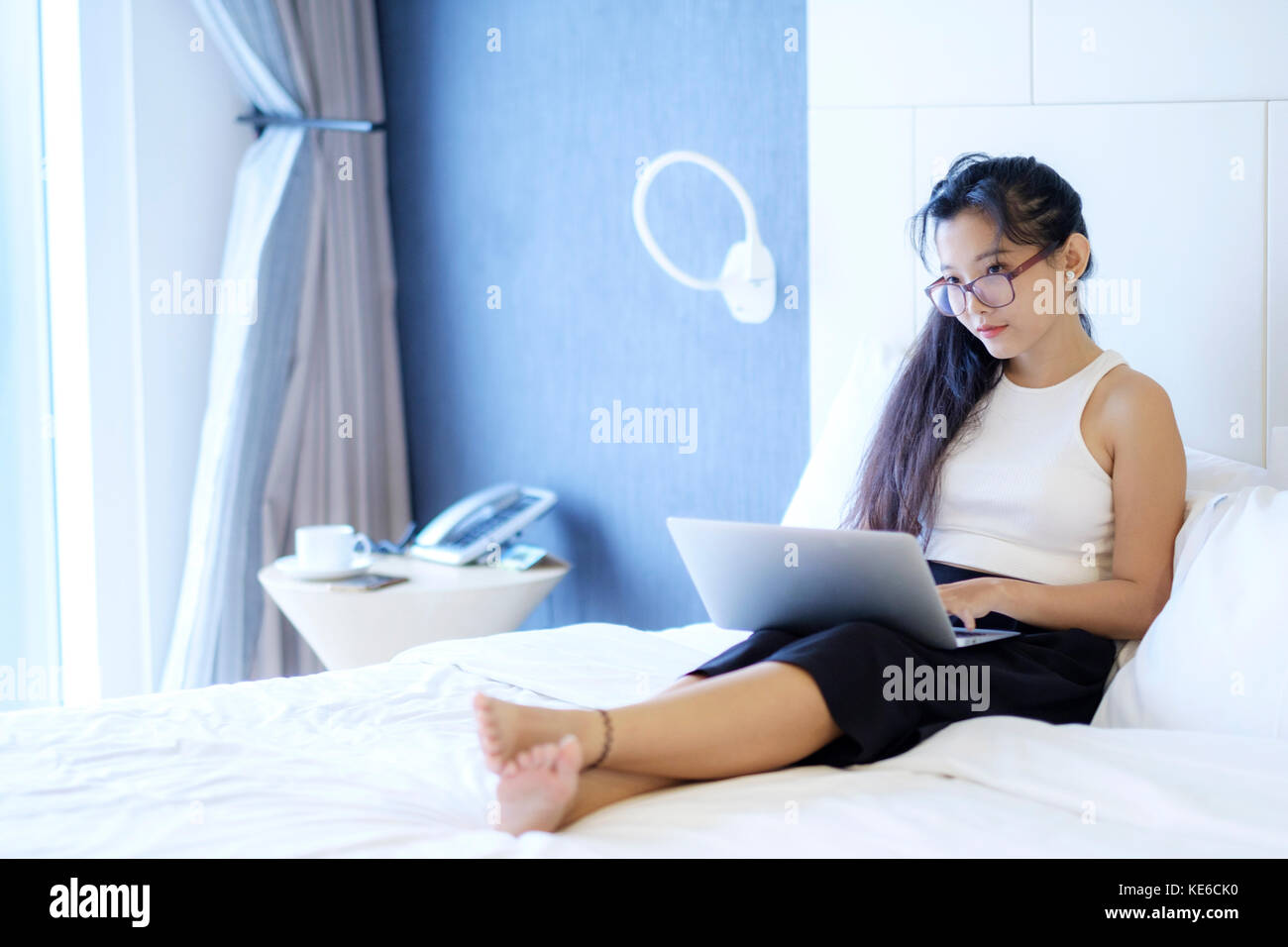 Young Asian business woman working in her hotel room - Stock Image
