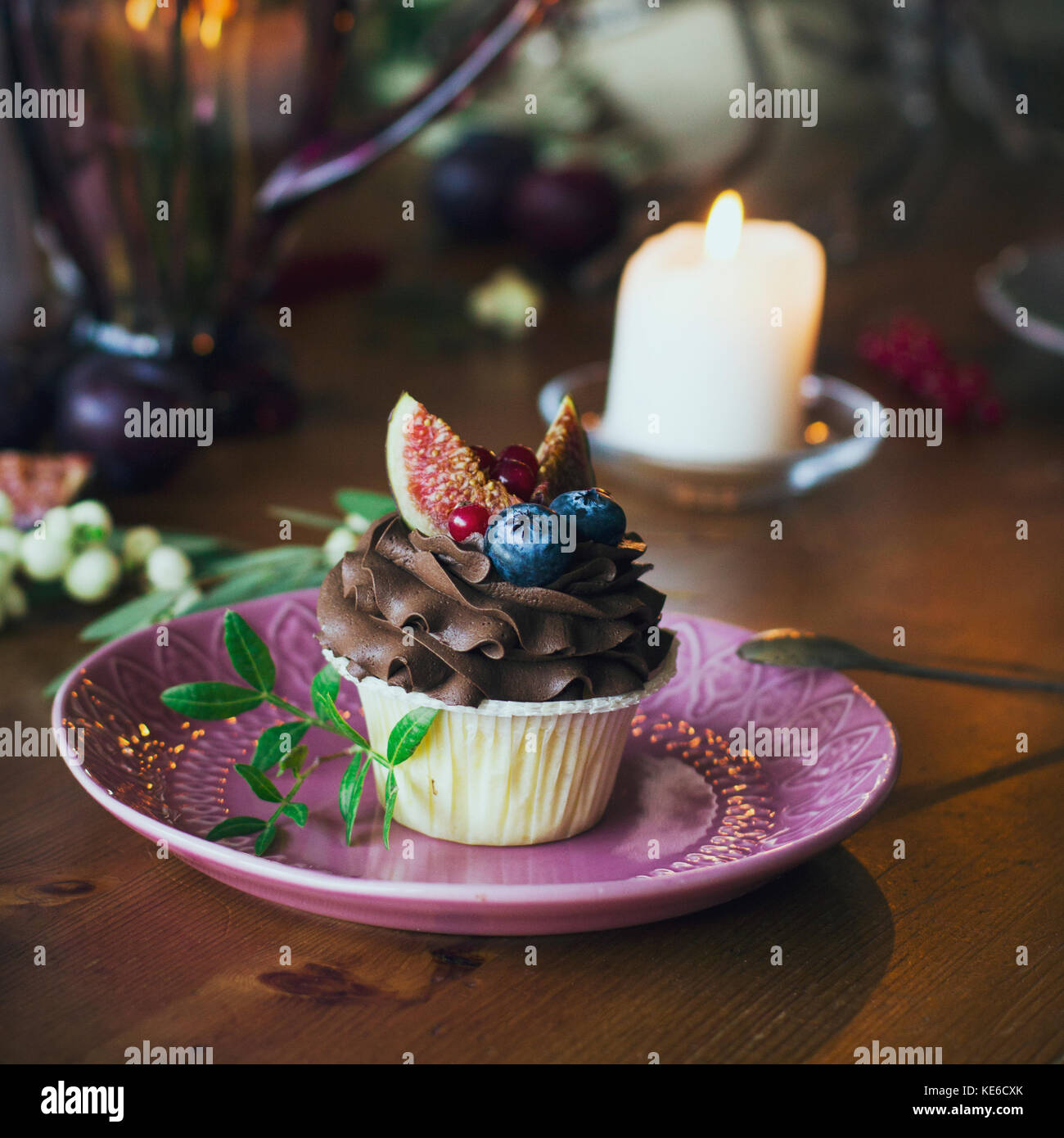 Chocolate cupcake with figs and berries on festive table - Stock Image