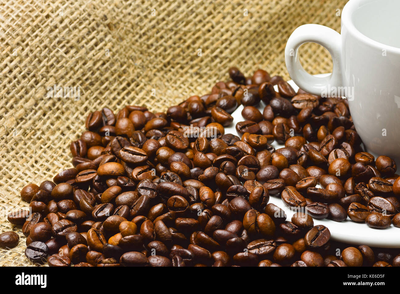 Close-up photo of grains of roasted black coffee with white porcelain cup on jute bags with blurred background and - Stock Image