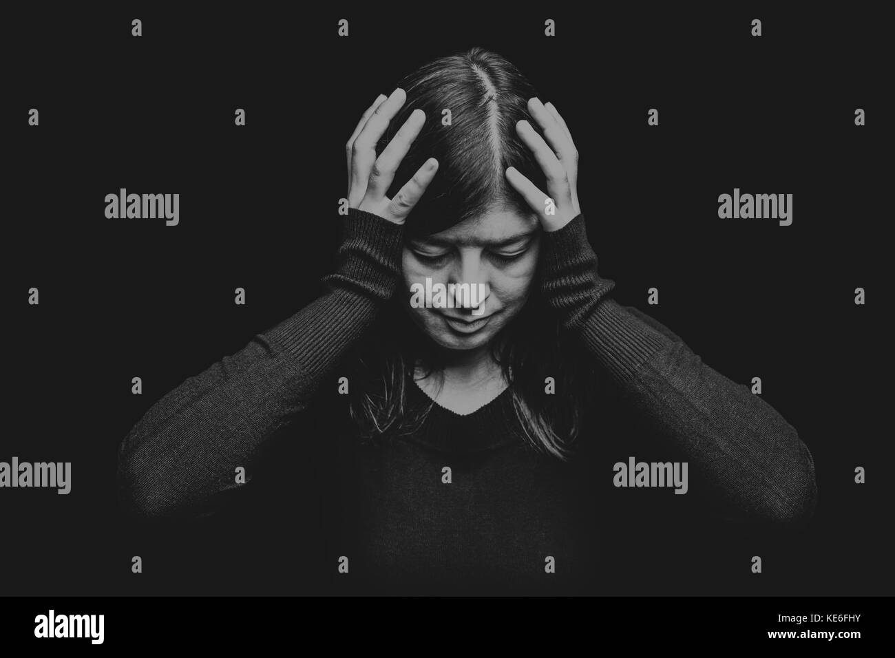 Distressed woman holding the head with the hands on a black or dark background. migraine headache pain depression - Stock Image