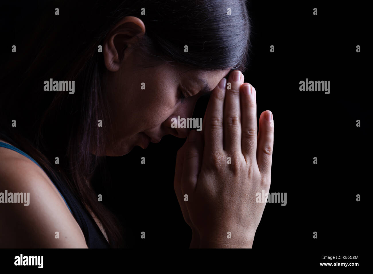 Faithful woman praying, hands folded in worship to god with head down and eyes closed in religious fervor, on a - Stock Image