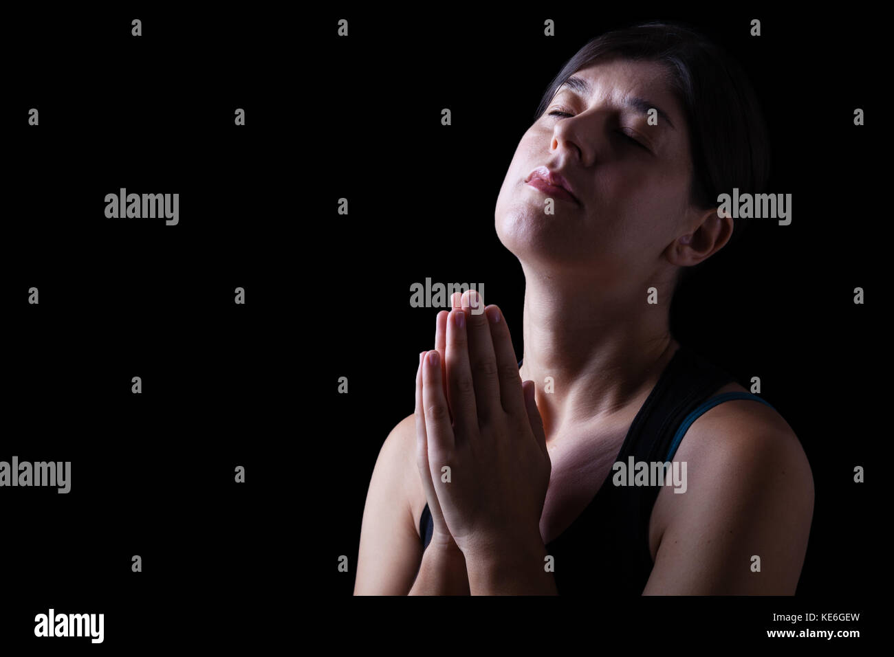 Faithful woman praying and feeling the presence or being touched by god. Hands folded in worship, head up and eyes - Stock Image