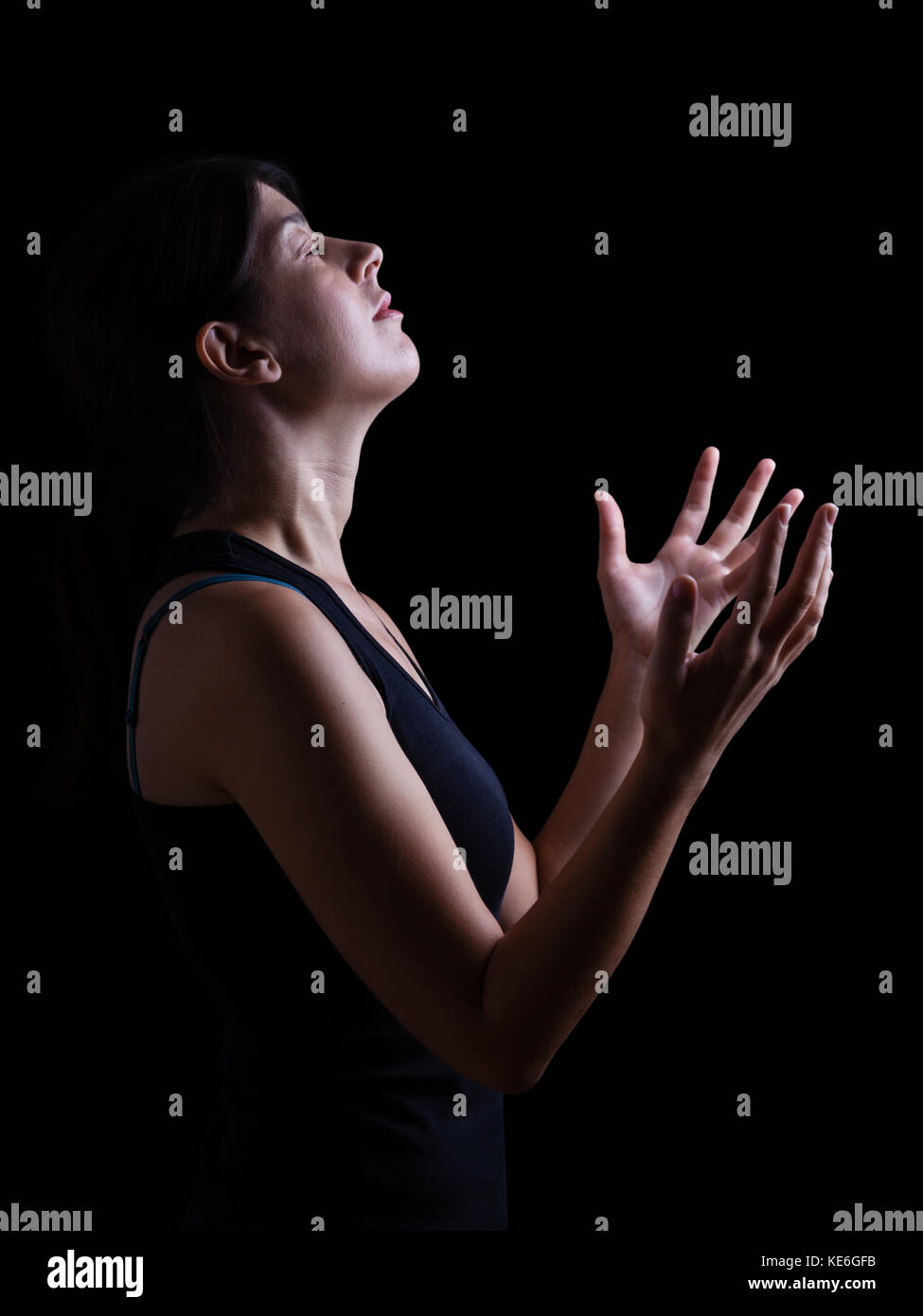 Low key of a faithful woman praying and feeling the presence or being touched by god. Arms outstretched in worship, - Stock Image