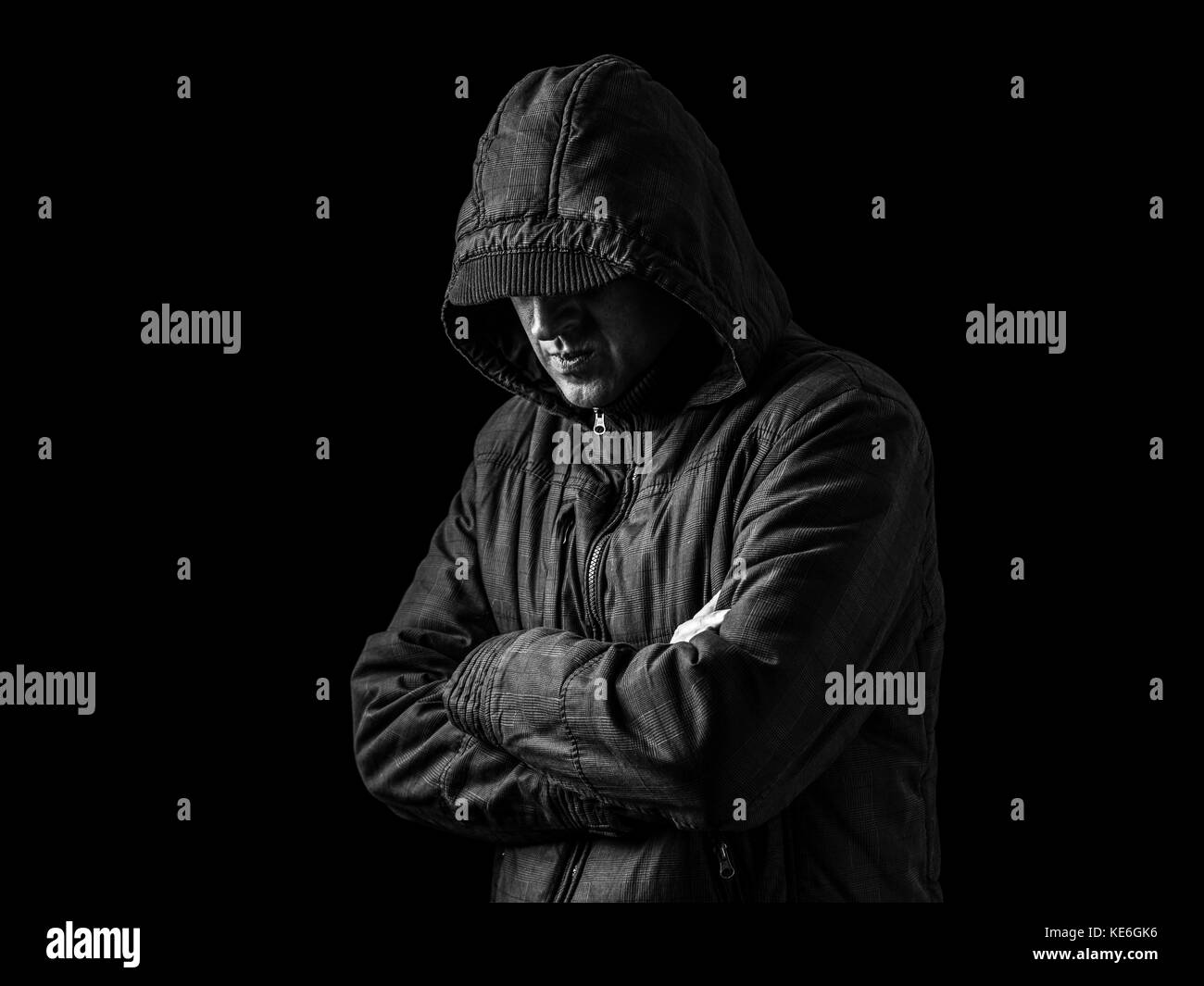 Lonely, depressed, fragile man hiding face, arms crossed, standing in the darkness. Low key, black background / - Stock Image