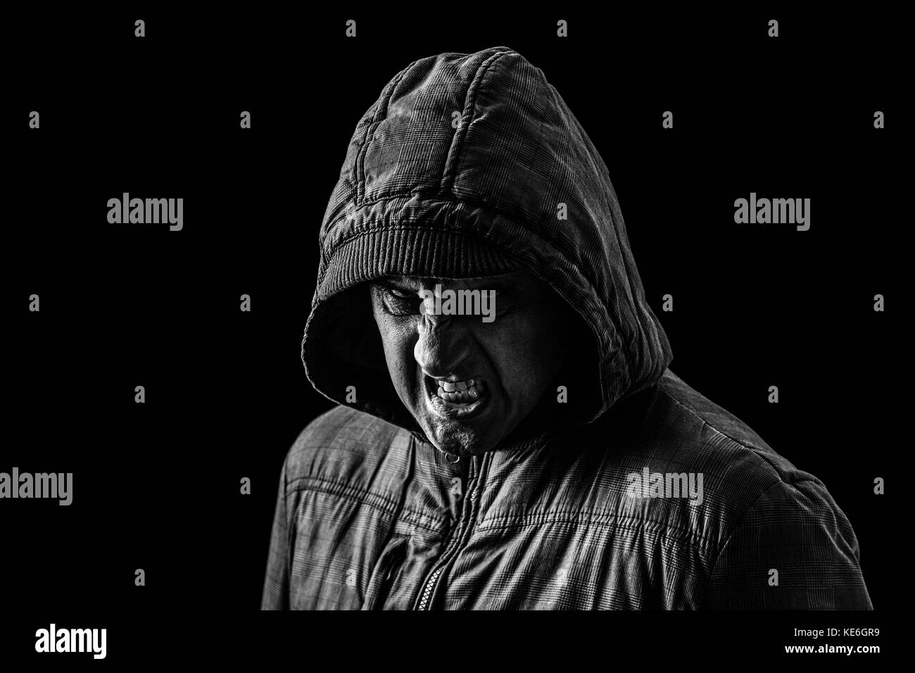 Very angry, aggressive, creepy man hiding the shadows, standing in the darkness.black background / creepy dangerous - Stock Image