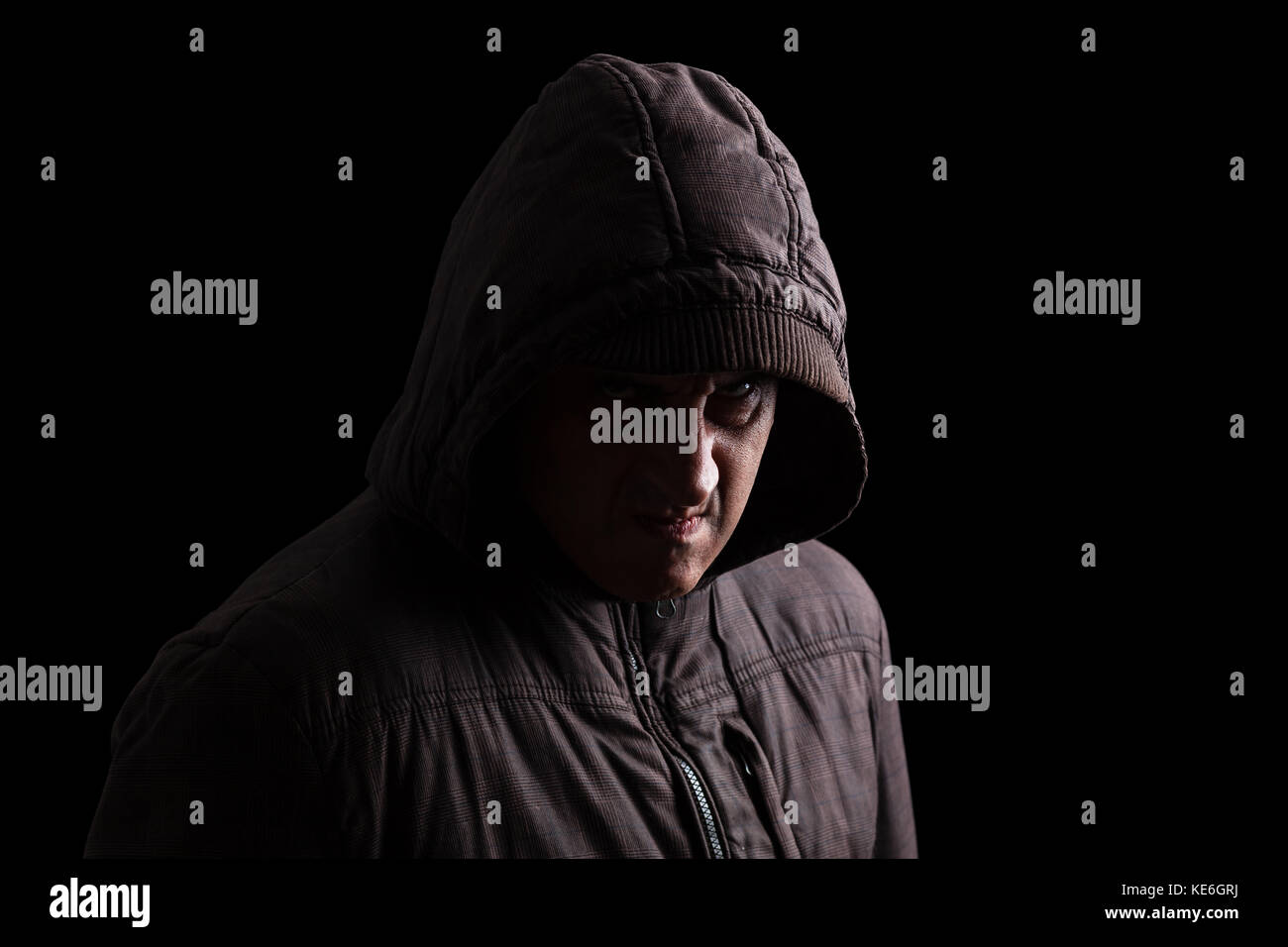Man with repressed anger and violent instinct hiding in shadows. Standing in the darkness / angry passive aggressive - Stock Image