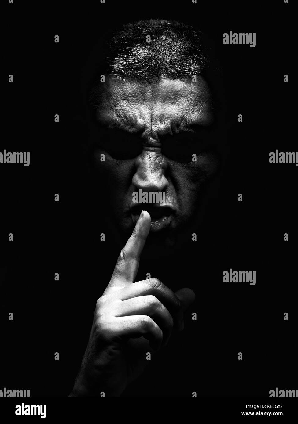 Furious mature man with aggressive look making silence sign in violent and threatening way. Black background / rage - Stock Image
