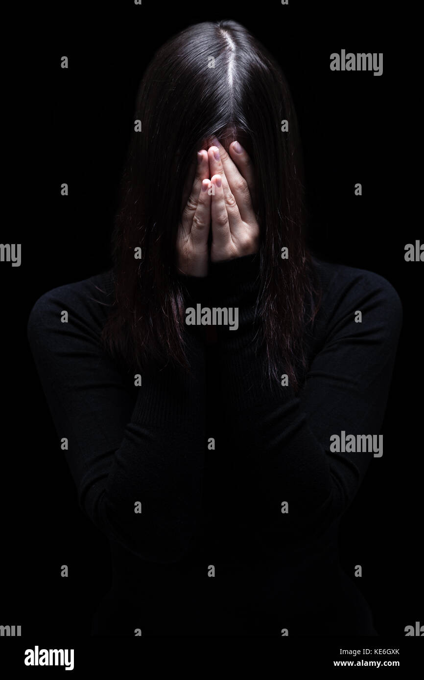 Emotional woman crying and covering face with hands hiding tears. black background / victim depression depressed - Stock Image