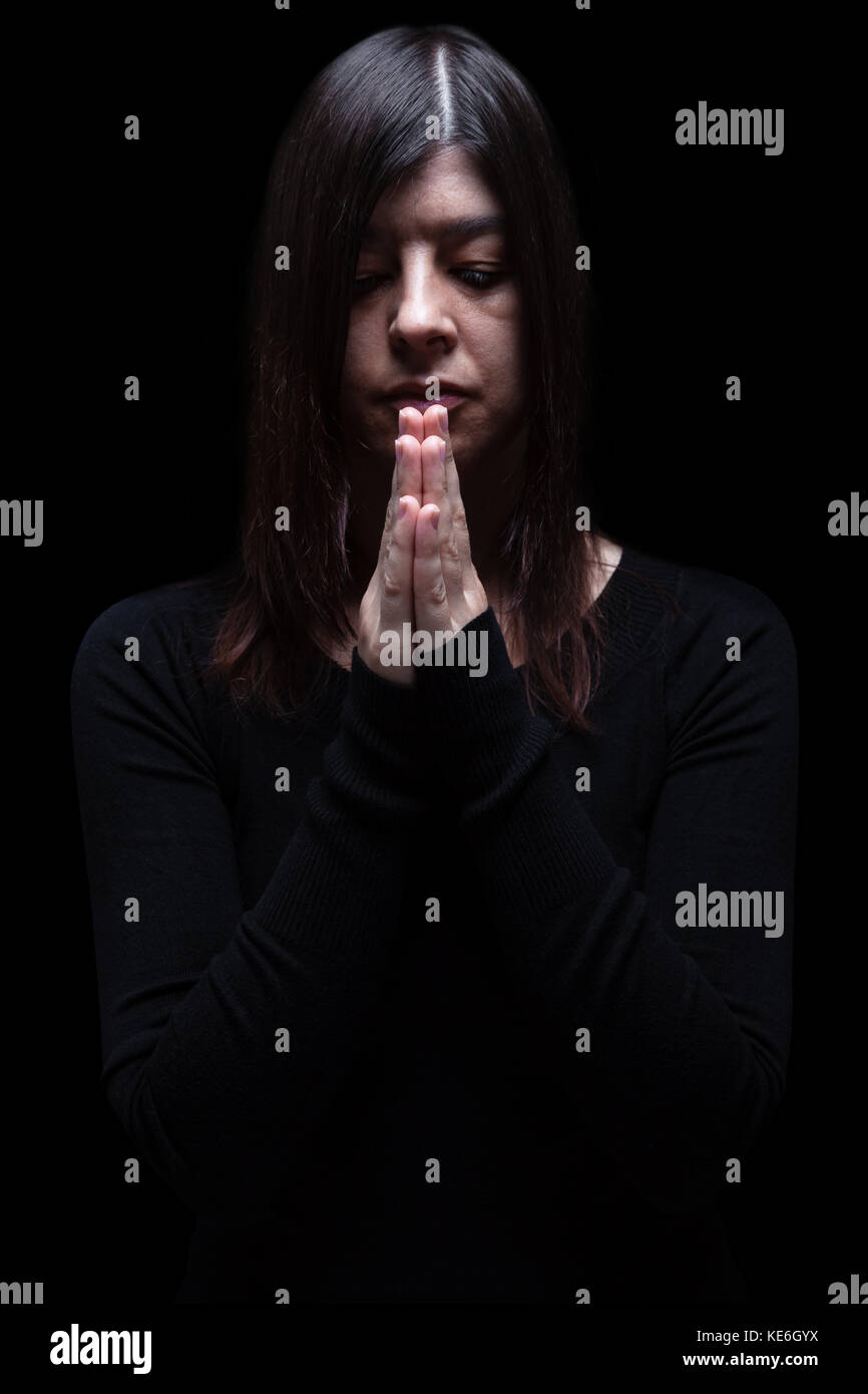 Mourning woman praying with hands folded in worship to god, looking down, eyes closed suffering. black background - Stock Image