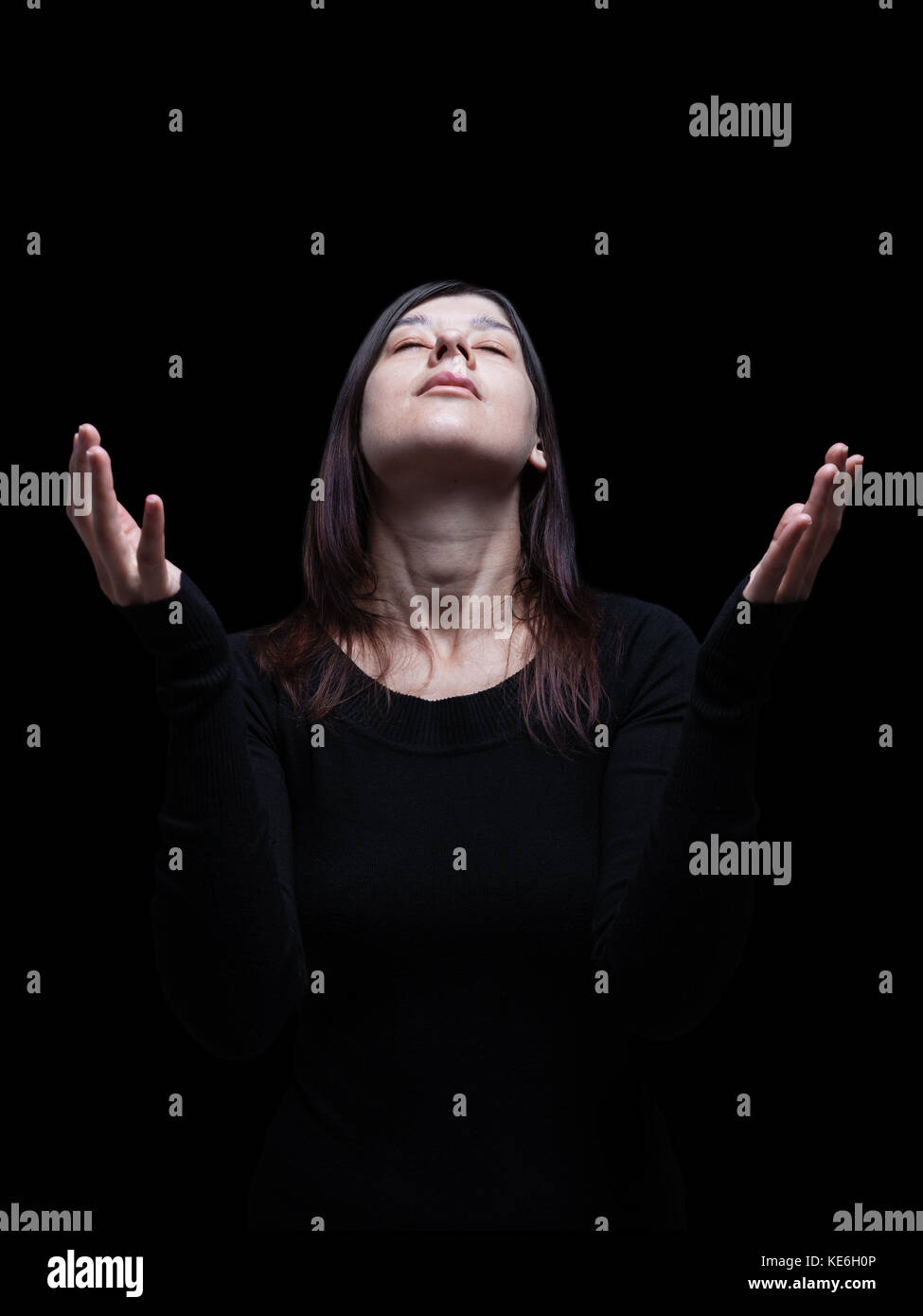 Mourning woman praying with arms outstretched in worship to god. Looking up, eyes closed in suffering. Black background - Stock Image