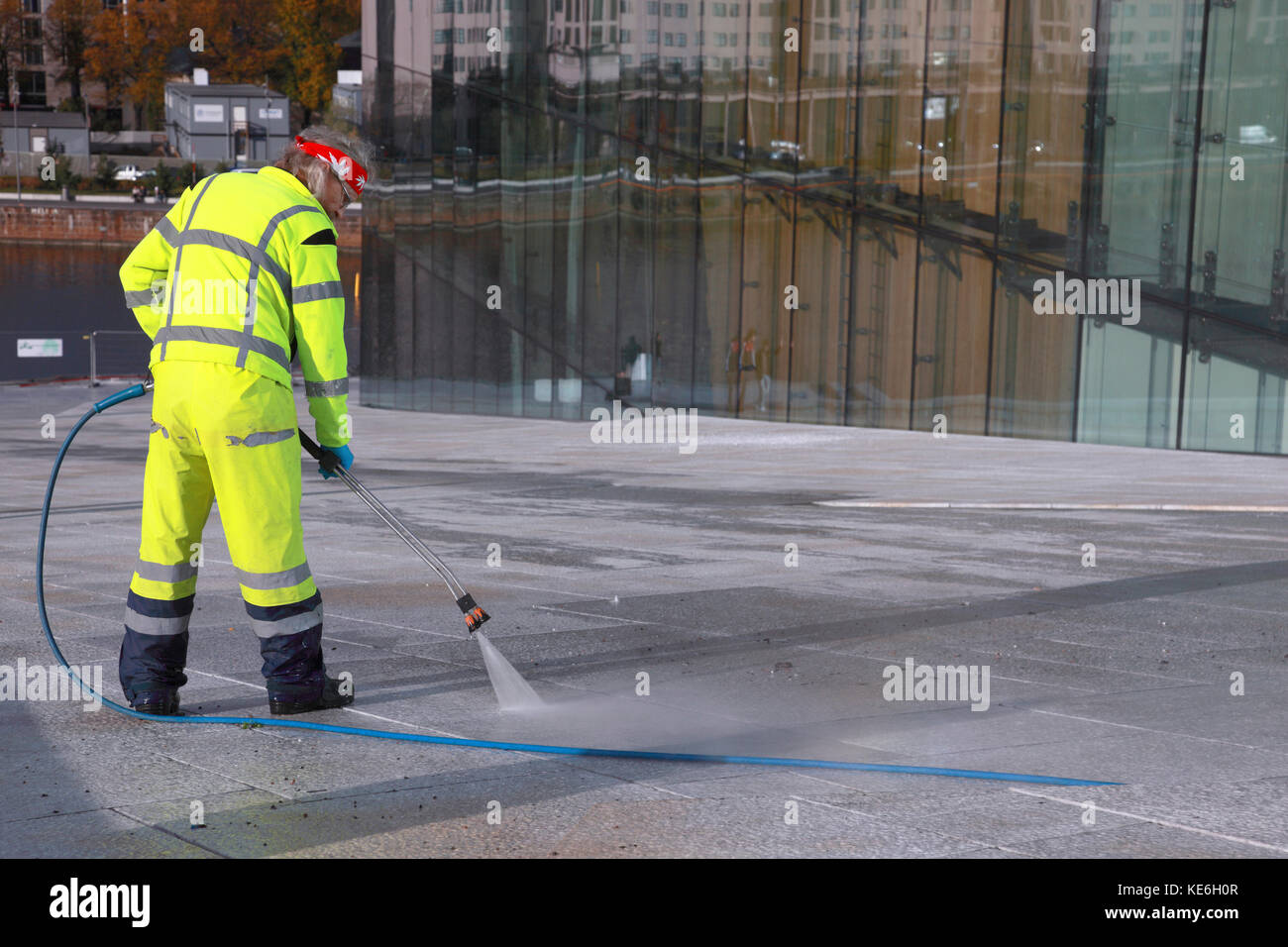 A man using a high pressure power wash to clean the white granite and marble of Oslo opera house, Norway - Stock Image