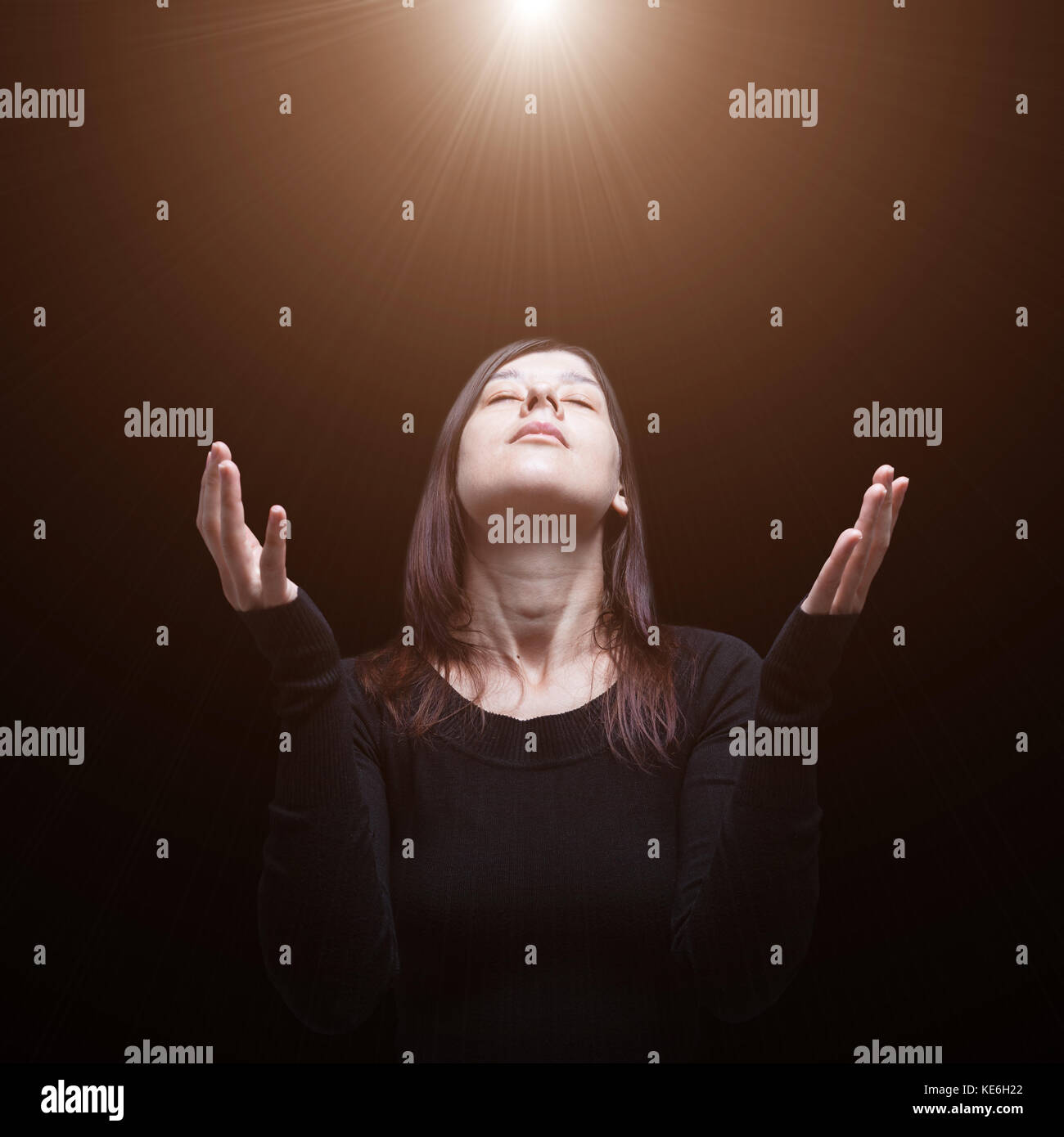 Mourning woman praying, arms outstretched in worship to god