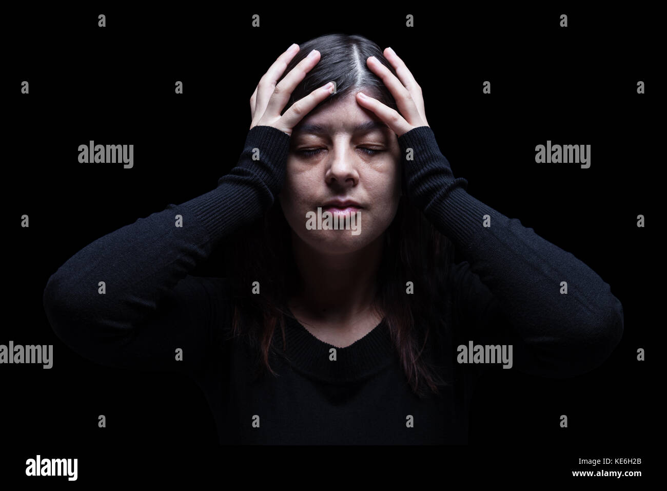 Distressed woman holding head with hands. Black background / Migraine headache pain depression depressed despair - Stock Image