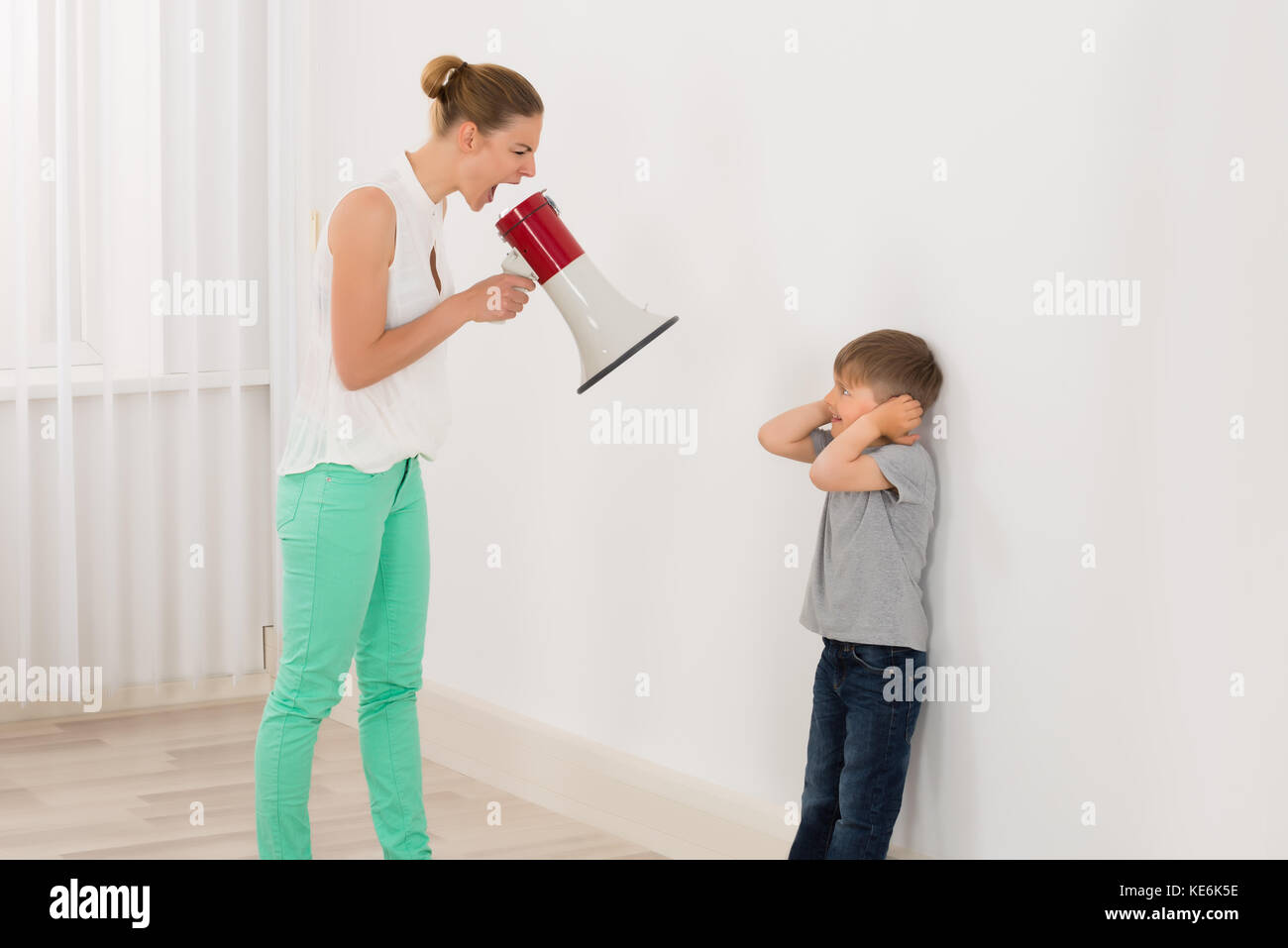 Mother Screaming At Her Son Through Megaphone - Stock Image