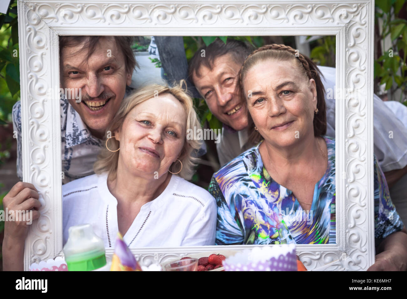 Group of embracing cheerful active seniors having fun during backyard party - Stock Image