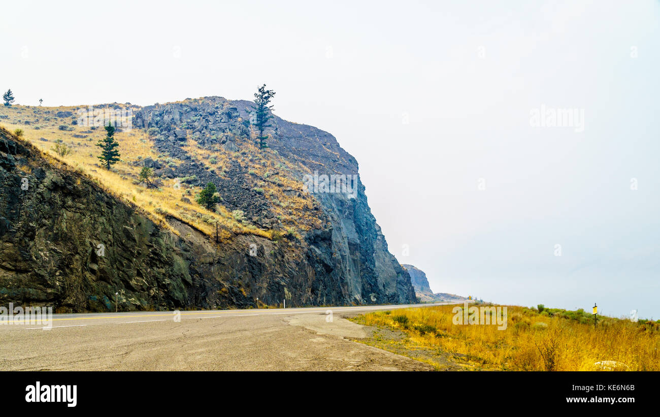 Smoke hanging over the Trans Canada Highway, along Kamloops Lake in British Columbia. The smoke is from the many - Stock Image