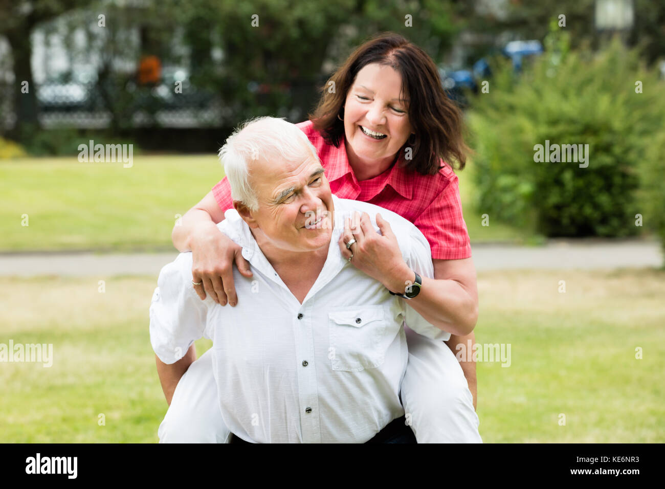 Portrait Of A Happy Senior Man Piggybacking His Wife - Stock Image