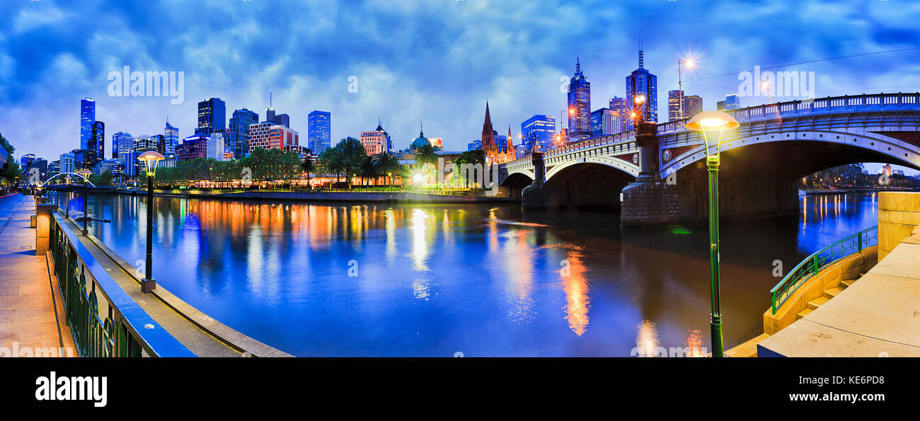 Princes bridge across Yarra river to Flinders station and Melbourne CBD dark at sunrise with bright street lights and skyscrapers illumination reflect Stock Photo