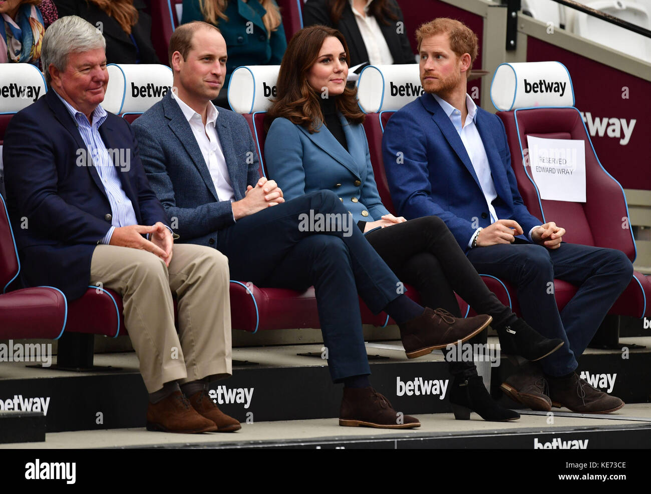 Sir Keith Mills chairman of the Royal Foundation sits with the Duke and Duchess of Cambridge and Prince Harry at - Stock Image