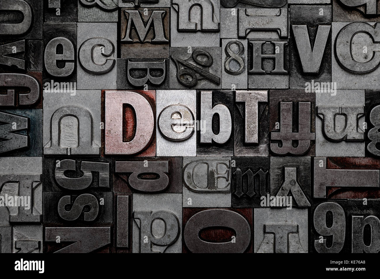 The word Debt made from old metal letterpress letters - Stock Image