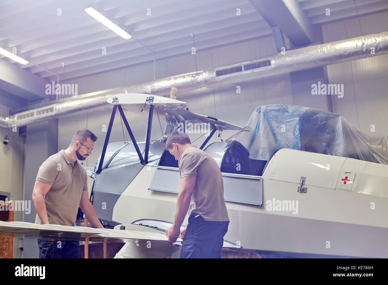 Male engineers assembling airplane in hangar Stock Photo