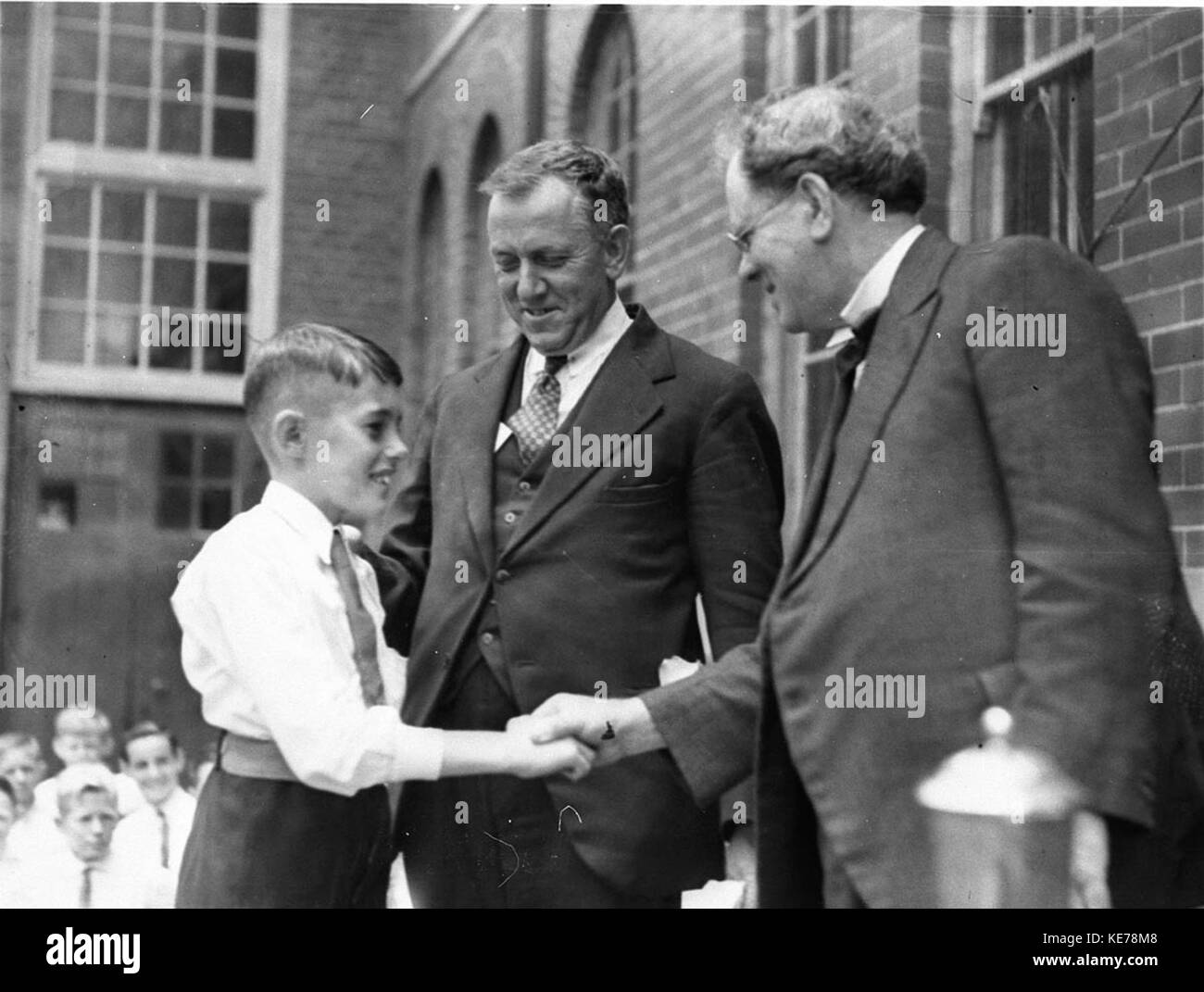 43234 Director of Education G Ross Thomas shakes hands with the dux of Drummoyne Primary School - Stock Image