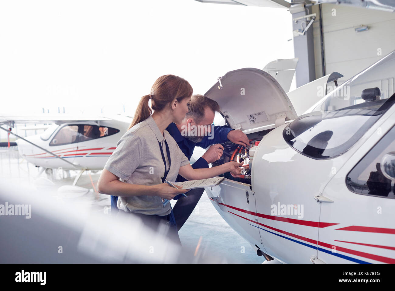 Engineer mechanics working on airplane engine in hangar Stock Photo