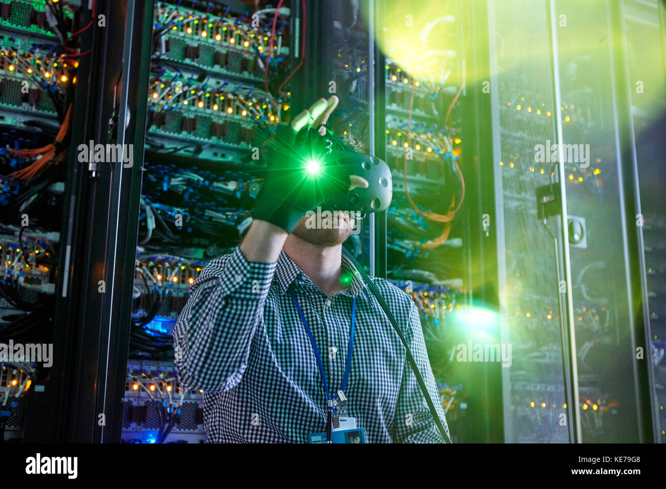 Male computer programmer using virtual reality simulator glasses and glowing glove in server room - Stock Image