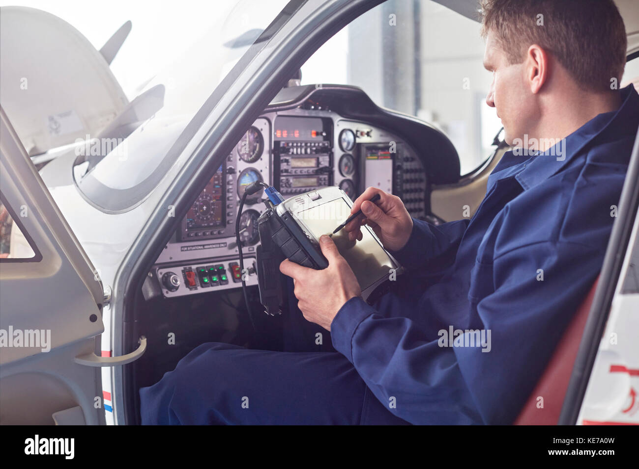 Male engineer checking diagnostics with digital tablet in airplane cockpit - Stock Image