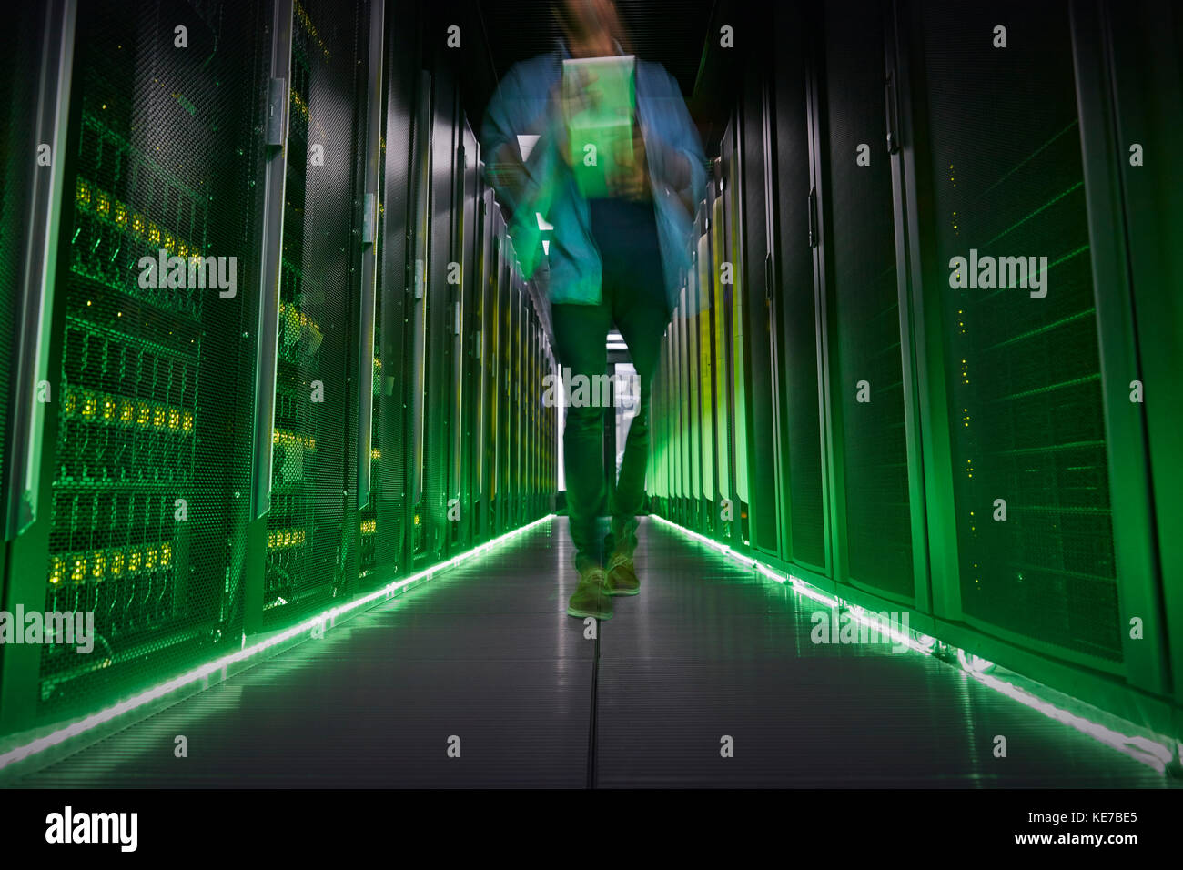 IT technician walking in dark, glowing server room - Stock Image