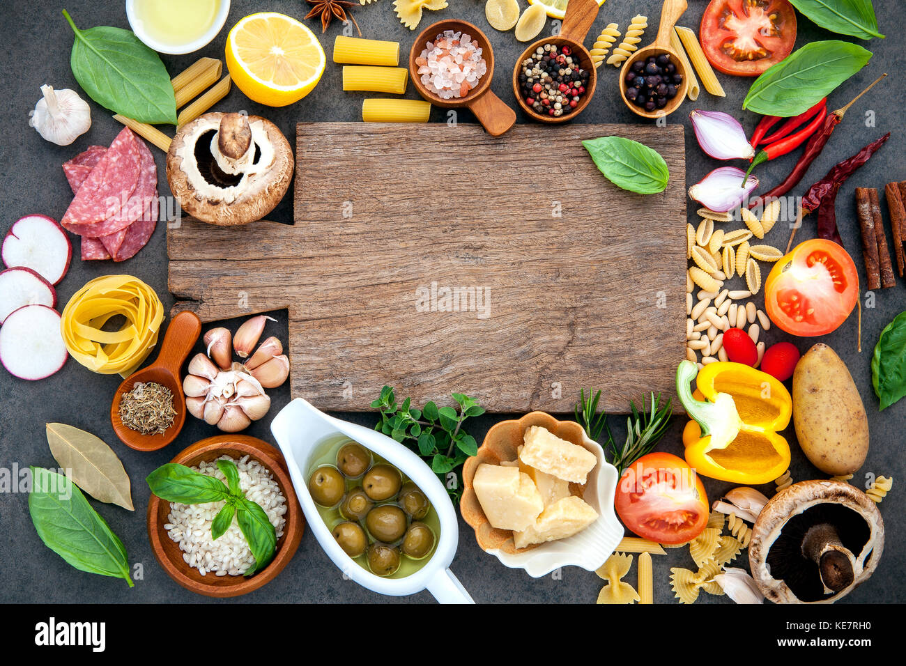 Italian food cooking ingredients on dark stone background with cutting board flat lay and copy space. - Stock Image