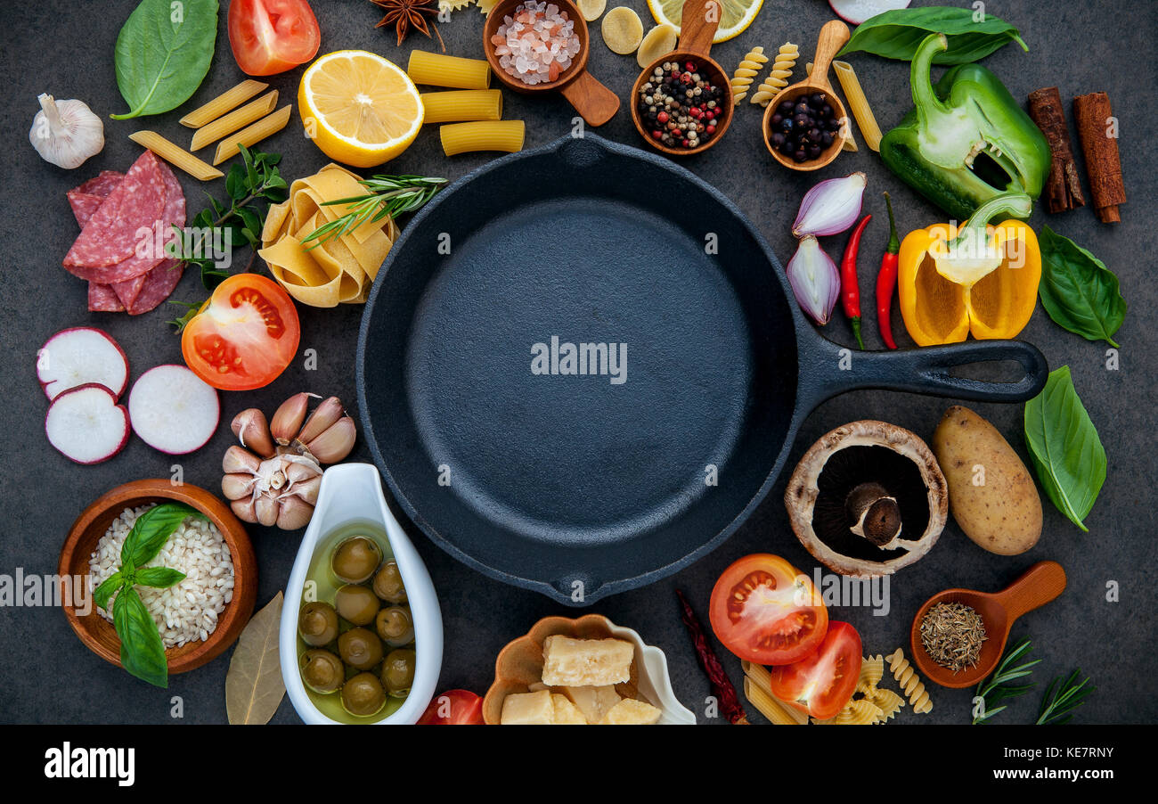 Italian food cooking ingredients on dark stone background with iron pan flat lay and copy space. - Stock Image