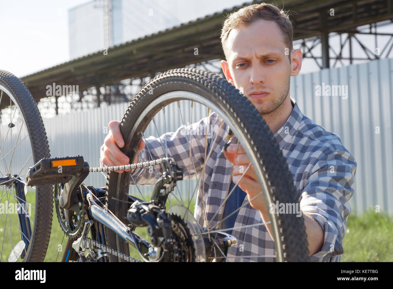 A concentrated craftsman is diagnosing bike malfunctions on the street - Stock Image