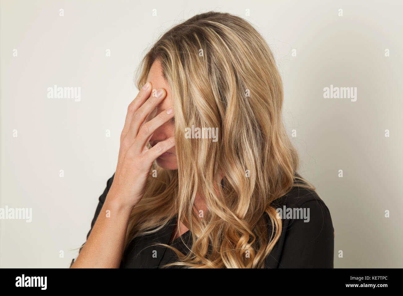 Woman With Blond Hair Hiding Her Face With Her Hand; Connecticut, United States Of America - Stock Image