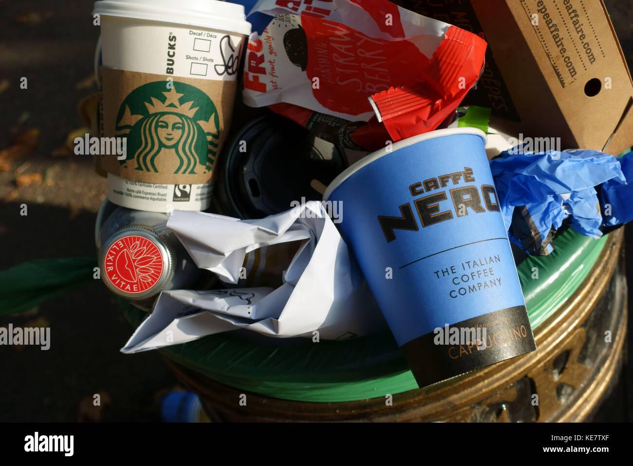 Non-recyclable coffee shop take away cups in street rubbish bin, London - Stock Image