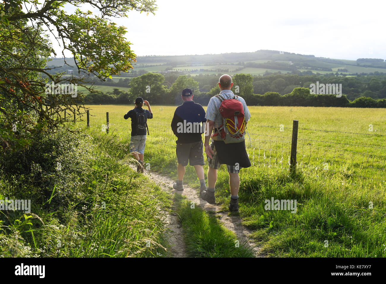 Three middle-aged men walking across the South Downs way between Winchester and Eastbourne England as the sun sets - Stock Image