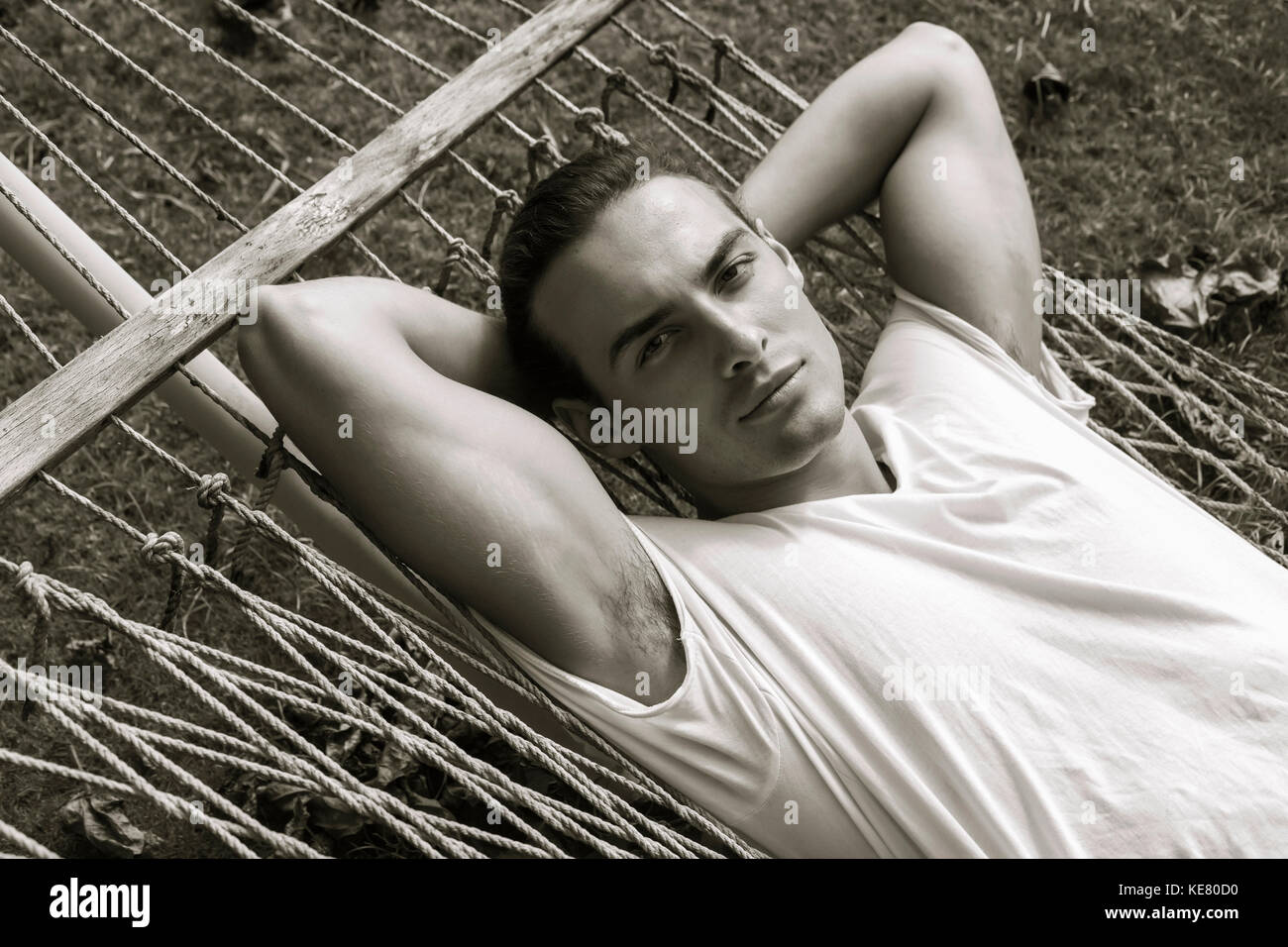 A young man lying on a hammock looking at the camera; Hawaii, United States of America Stock Photo