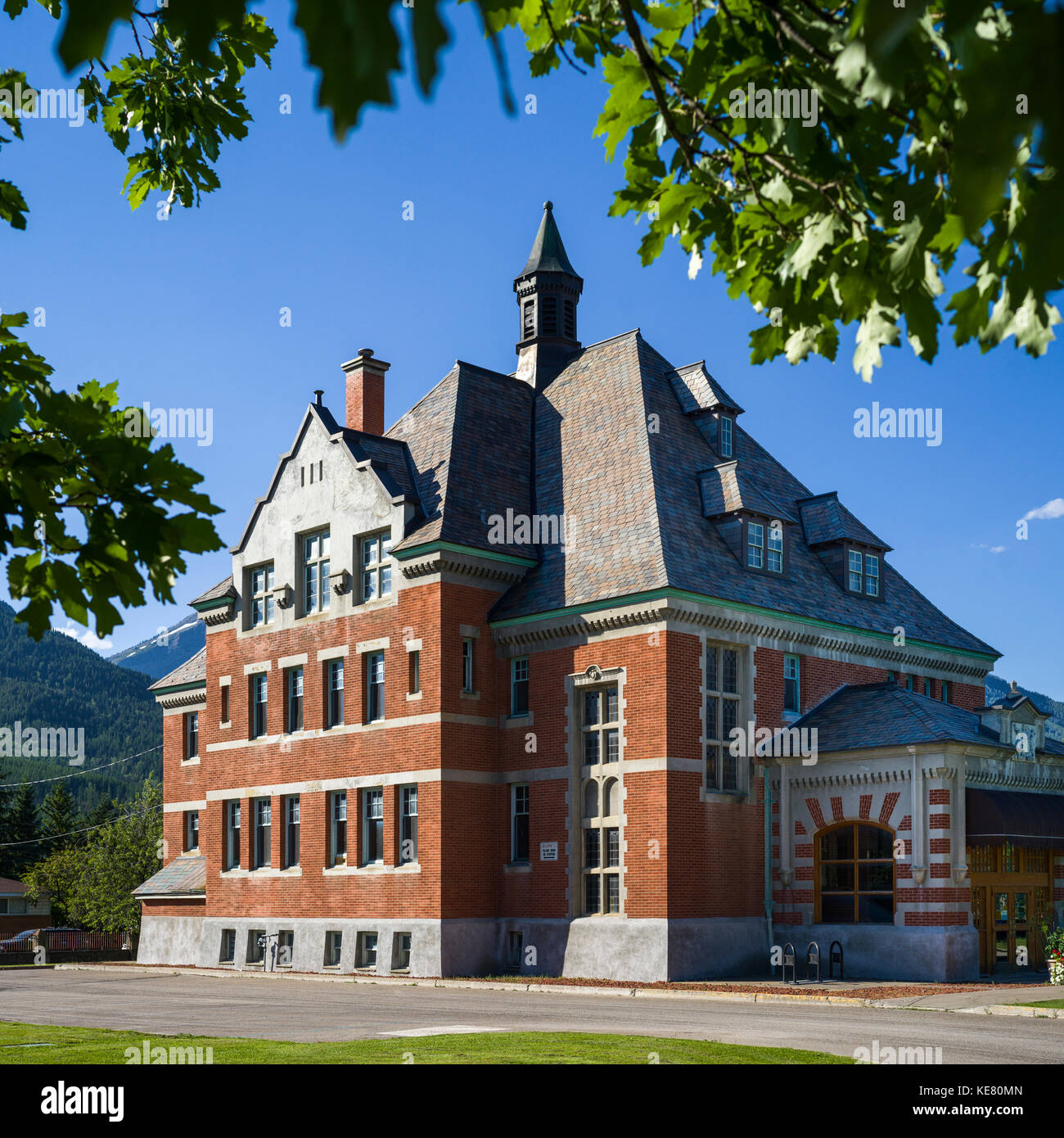 The Fernie Court House under a blue sky framed with trees; Fernie, Alberta, Canada - Stock Image
