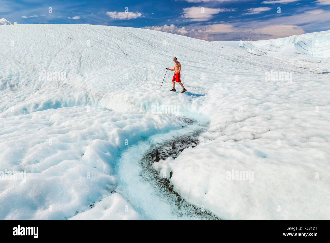 A shirtless man in a bathing suit walks across the surface of Root Glacier with trekking poles in Wrangell-St. Elias - Stock Image