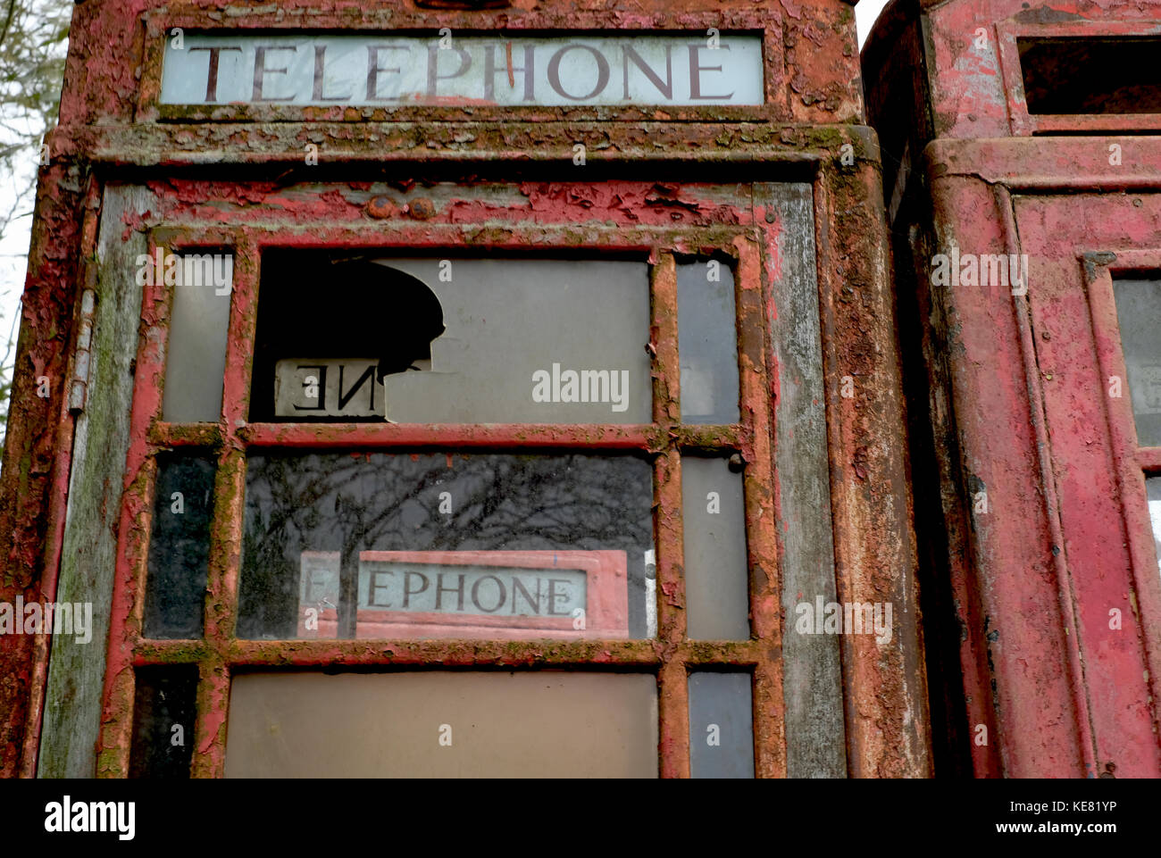 Close up of abandoned red telephone kiosks in reclamation yard. - Stock Image