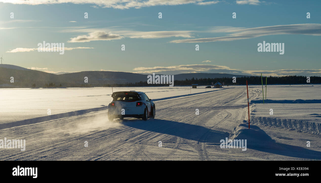 A Car Drives Over A Snow-Covered Road Under A Blue Sky With Cloud And Mountains In The Distance; Arjeplog, Norrbotten - Stock Image