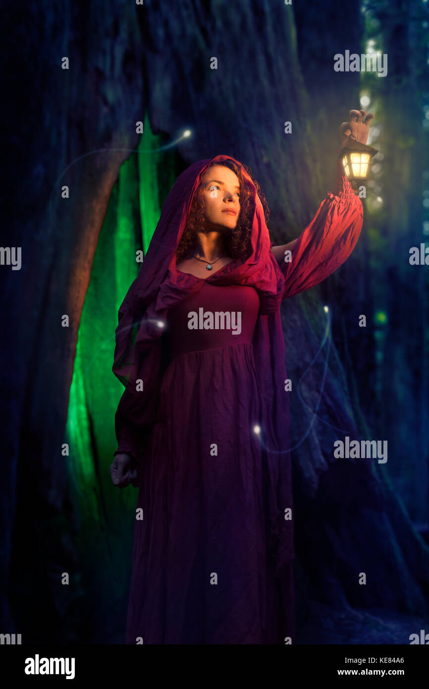 Artistic fairy tale portrait of a woman in a red hooded dress with a lantern in a forest at night with fireflies - Stock Image